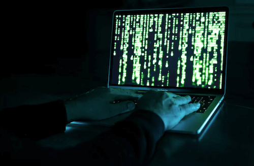In this photo illustration, a hacker uses a computer.