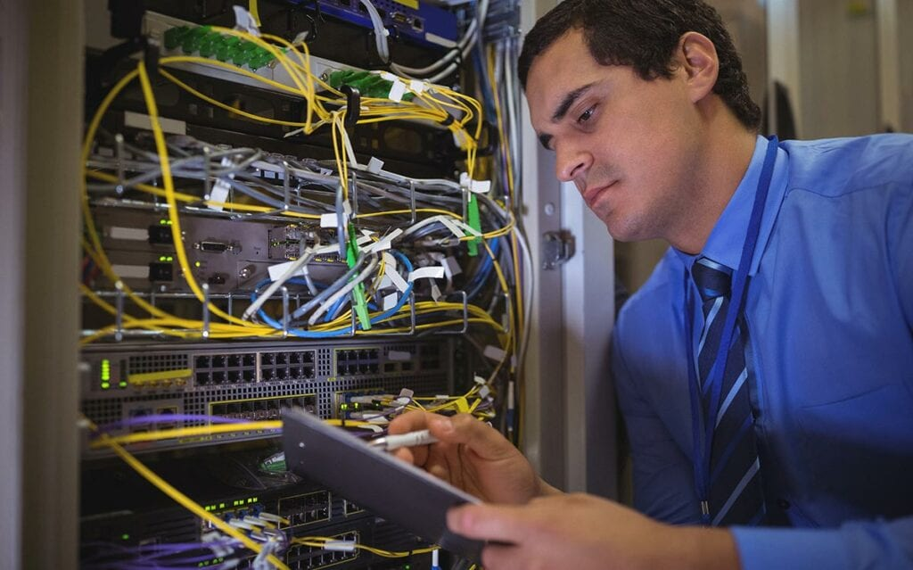 Person by network rack looking at tablet