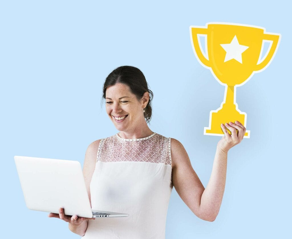 Women with laptop holding up a trophy